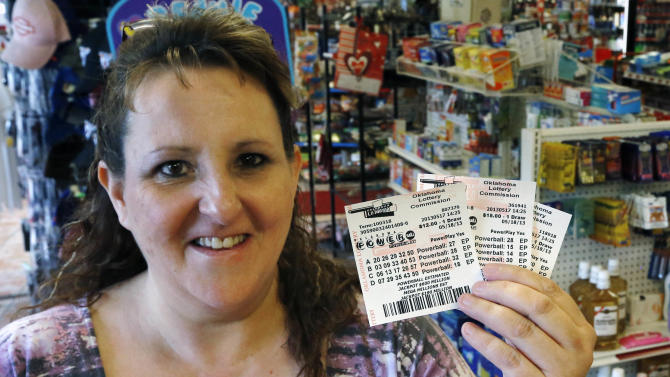 Cathy Raymond, of Oklahoma City, displays the Powerball Lottery tickets she purchased in Oklahoma City, Friday, May 17, 2013. Powerball officials say the jackpot has climbed to an estimated $600 million, making it the largest prize in the game's history and the world's second largest lottery prize.(AP Photo/Sue Ogrocki)