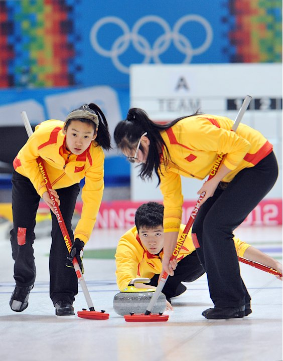 China's Bai Yang, center, l ooks on as his teammates Cao Ying, left, and Yang Ying work on the stone while playing against the United States during a mixed team curling event at the first winter Youth