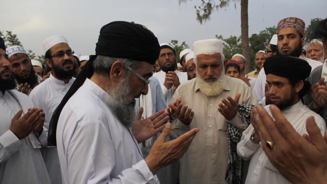 People offer prayers for two people who were killed by police in Texas, as they hold a special service at a public park in Peshawar, Pakistan, Tuesday, May 5, 2015. About 50 Islamists held the special service Tuesday in northwest Pakistan for the two men killed in the U.S. after they opened fire at a cartoon contest featuring images of the Muslim Prophet Muhammad. The cleric Mohammad Chishti led the service for Elton Simpson and Nadir Soofi. (AP Photo/Mohammad Sajjad)