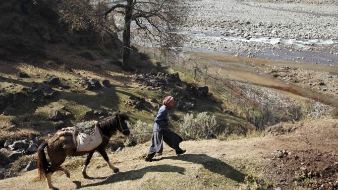 An Indian man walks with his horse near the border village of Dallan, in Poonch, 250 kilometers (155 miles) northwest of Jammu, India, Tuesday, Jan. 15, 2013. India's army chief Gen. Bikram Singh on Monday accused Pakistan of planning an attack in which two Indian soldiers were killed in the disputed Kashmir region last week, and warned of possible retaliation. (AP Photo/Channi Anand)