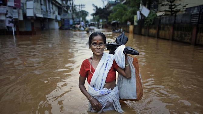 An Indian woman wades through the floodwaters in Gauhati, India, Friday, June 27, 2014. Several people were killed due to electrocution and landslides triggered by incessant rains in India's northeastern state of Assam, according to local reports. (AP Photo/Anupam Nath)