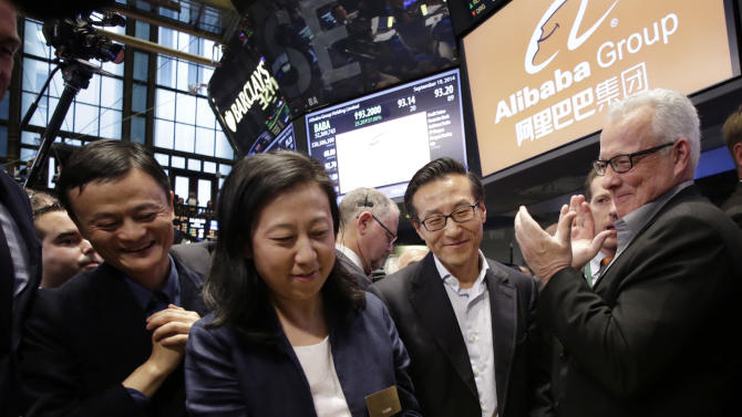 """Chief Financial Officer of Alibaba Group Maggie Wu strikes a bell as Jack Ma, left, founder of Alibaba, watches during the company's IPO at the New York Stock Exchange, Friday, Sept. 19, 2014 in New York. The stock is to start trading Friday under the ticker """"BABA."""" (AP Photo/Mark Lennihan)"""