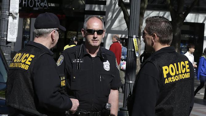 "Seattle Police officers, including Craig Williamson, center, and his explosives detection dog, ""Dennis"" confer as during a patrol in downtown Seattle, Monday, April 15, 2013, in reaction to explosions at the Boston Marathon finish line earlier in the day. A Seattle Police blog posting said that although there was no indication of a direct threat to Seattle, officers would be increasing patrols and activity around the city. (AP Photo/Ted S. Warren)"