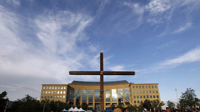 "A cross stands among people gathered for a vigil for victims of the movie theater mass shooting Sunday, July 22, 2012 at the Aurora Municipal Center in Aurora, Colo. 12 people were killed and 58 were injured in a shooting during an early Friday premiere of ""The Dark Knight Rises."" (AP Photo/Alex Brandon)"