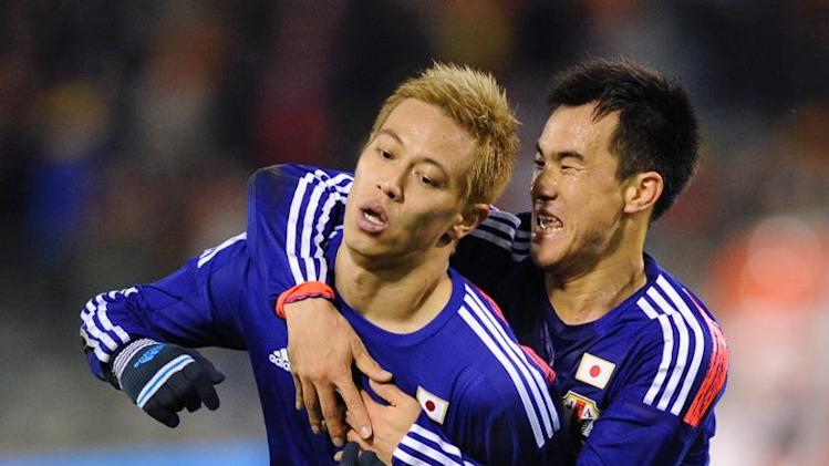 Japan midfielder Keisuke Honda (left) celebrates after scoring in a friendly against Belgium at the King Baudouin stadium, on November 19, 2013 in Brussels