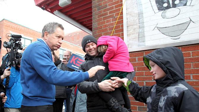 U.S. Republican presidential candidate and Ohio Governor John Kasich bumps fists with Cameron Patronick, 8, of Nashua, after a campaign stop at the Red Arrow Diner in Manchester