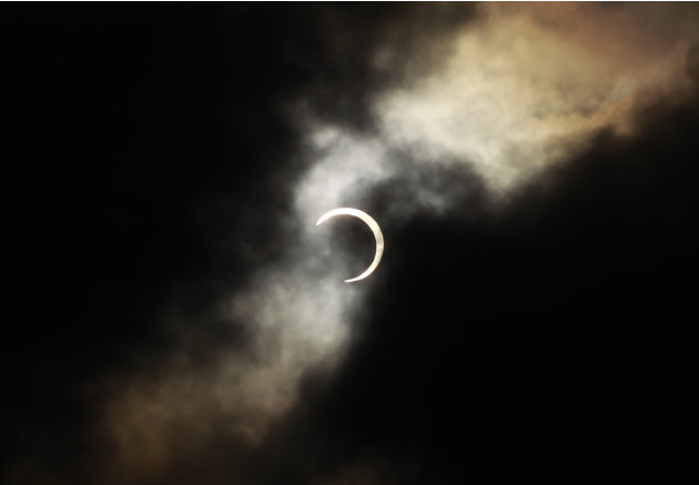An annular solar eclipse appears during a break in clouds over Taipei, Taiwan, Monday, May 21, 2012. The annular eclipse, in which the moon passes in front of the sun leaving only a golden ring around
