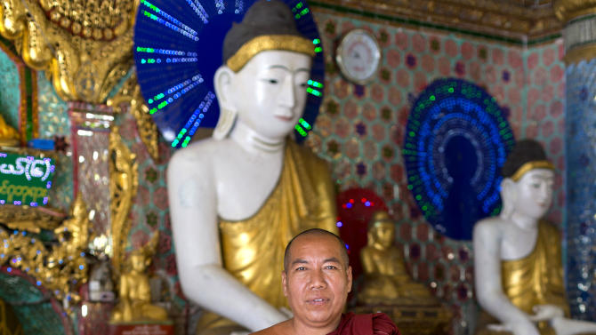 "In this picture taken on Thursday, Nov. 15, 2012, Buddhist monk Wizaya poses for a photograph at Shwedagon Pagoda in Yangon, Myanmar. ""I think America can work for the people. China only works for the government,"" said Wizaya, a 47-year-old monk. Word of U.S. President Barack Obama's historic visit has spread quickly around Yangon, which is readying itself with legions of hunched workers painting fences and curbs, pulling weeds and scraping grime off old buildings in anticipation of the president's Monday arrival. (AP Photo/Gemunu Amarasinghe)"