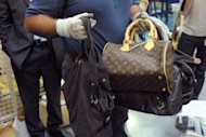 A French customs officer shows seized counterfeit handbags prior their destruction in May 2012. The counterfeiting of goods, according to the United Nations Office on Drugs and Crime, brought in $250 billion annually to organised crime groups