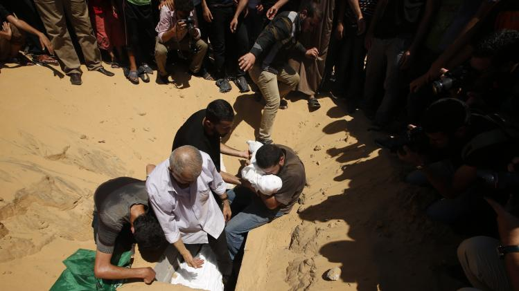 Palestinians bury the bodies of the wife of Deif, Hamas's military leader, and his infant son Ali, at a cemetery in Beit Lahiya in the northern Gaza Strip