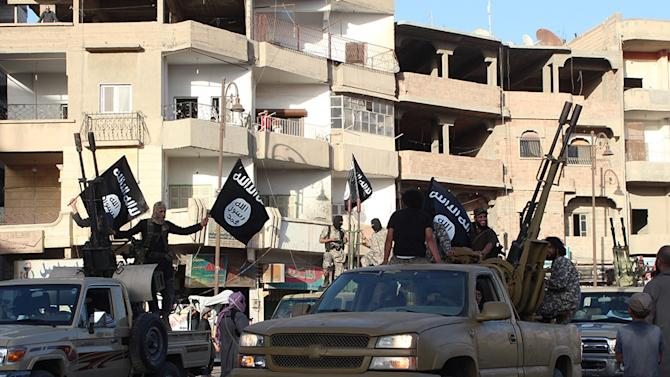 An image made available by Jihadist media outlet Welayat Raqa on June 30, 2014, allegedly shows a member of the IS (Islamic state) militant group parading in a street in the northern rebel-held Syrian city of Raqa