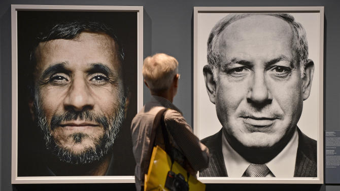 """FILE - In this Wednesday, Sept. 19, 2012 file photo, a visitor looks at portraits of Iran's President Mahmoud Ahmadinejad and Israel's Prime Minister Benjamin Netanyahu during the exhibition """"faces of power"""" by Greek photo artist Platon Antoniou, shown at the Photokina 2012 in Cologne, Germany. Israeli Prime Minister Benjamin Netanyahu heads to the United Nations this week with a single item on his agenda: Iran. Netanyahu is convinced the Islamic Republic isn't taking American vows to block it from acquiring nuclear weapons seriously and that time is quickly running out to stop them. (AP Photo / Martin Meissner, File)"""