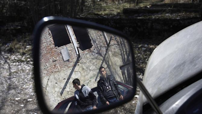 """Bosnian young men are reflected in a car mirror as they participate in a symbolic ceremony for the town of Drvar, some 400 Km (250 miles) west of Sarajevo, on Monday, March 4, 2013.  With candles, speeches and an obituary plastered on walls reading """"Town of Drvar 1883 - 2013,""""  the residents symbolically laid this town to rest in peace on Monday. Two months ago, the last company in Drvar closed down, sending the town's unemployment rate skyrocketing to around 80 percent.  The town had no chance to survive the double tragedies of the 1992-95 Bosnian war and then the global financial crisis which have joined to kill off this once lively community.(AP Photo/Amel Emric)"""