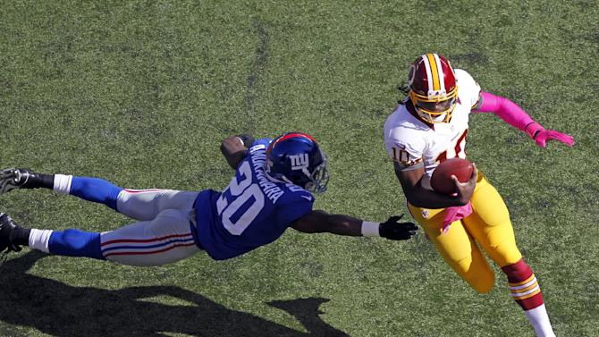 Washington Redskins quarterback Robert Griffin III (10) avoids a tackle by New York Giants cornerback Prince Amukamara (20) during the first half of an NFL football game on Sunday, Oct. 21, 2012 in East Rutherford, N.J. (AP Photo/Julio Cortez)