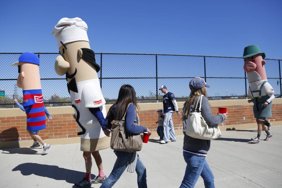 The racing sausages join fans on their way into Miller park before an Opening day baseball game between the Milwaukee Brewers and St. Louis Cardinals  Friday, April 6, 2012, in Milwaukee. (AP Photo/Jeffrey Phelps)