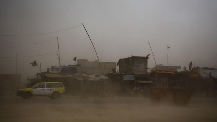 A taxi tries to make its way through a sandstorm that obscures the city of Kanadahar, Afghanistan, Sunday April 21, 2013. (AP Photo/Anja Niedringhaus)
