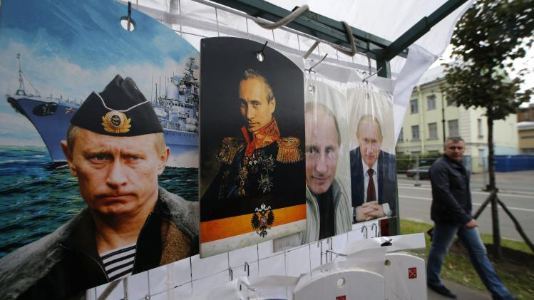 A man walks past cutting boards, that have been painted with images of Russia's President Vladimir Putin, at a street store in the center of St. Petersburg