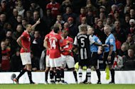 Manchester United players remonstrate with linesman John Flynn, right, and referee Michael Jones as a penalty is given after a tackle by Rio Ferdinand, left, on Newcastle United's Hatem Ben Afrfa during their English Premier League soccer match at Old Trafford Stadium, Manchester, England, Saturday Nov. 26, 2011. (AP Photo/Jon Super)