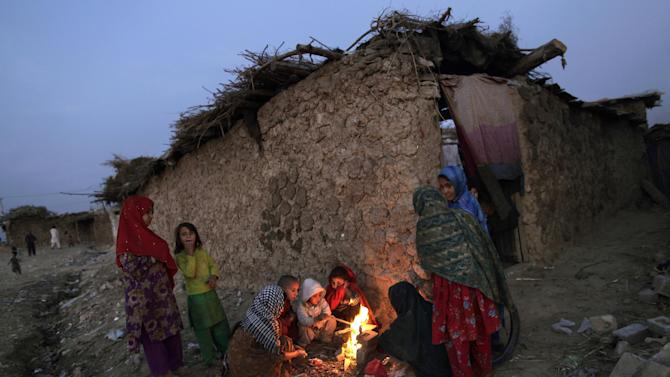 Afghan refugee children gather around a fire to warm themselves, in a slum on the outskirts of Islamabad, Pakistan, Monday, Nov. 26, 2012. (AP Photo/Muhammed Muheisen)