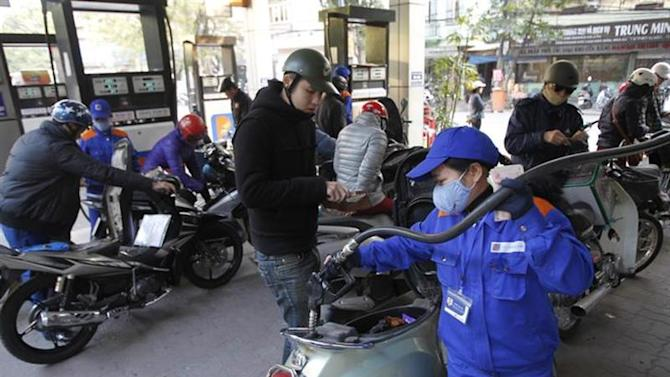 A woman pumps petrol into a motorcycle at a petrol station in Hanoi December 18, 2013. REUTERS/Kham/Files
