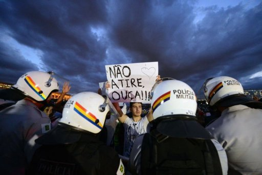 "A student holds a sign reading ""Don't shoot, listen!!!"" during a protest on June 17, 2013 in Brasilia"