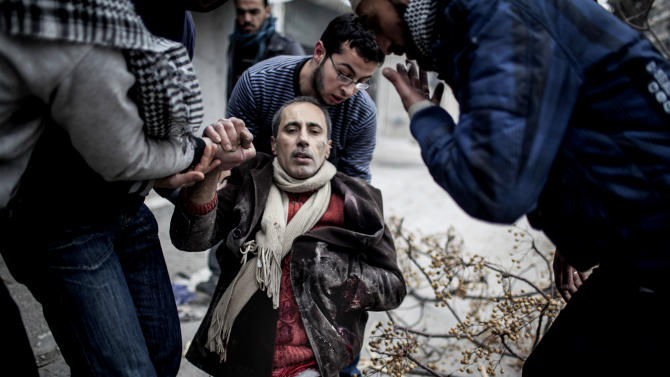Men help a wounded civilian after a mortar attack in the Saif al-Dawlah neighborhood of Aleppo, Syria, Sunday, Jan. 13, 2013. The revolution against the Syrian regime started in March 2011 with peaceful protests but morphed into a civil war that has killed more than 60,000 people, according to a recent United Nations estimate. (AP Photo/Andoni Lubaki)