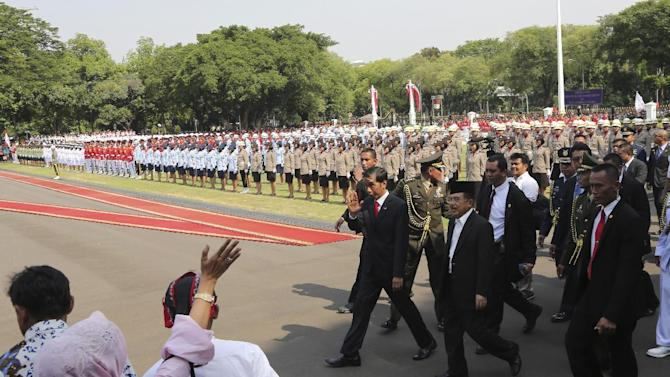 Indonesia's President Joko Widodo, left, waves as he walks with Vice President Jusuf Kalla, second right, at the presidential palace in Jakarta, Indonesia, Monday, Oct. 20, 2014. Widodo completed a journey from riverside shack to presidential palace on Monday, cheered through the streets following his inauguration by tens of thousands of ordinary Indonesians in a reminder to the opposition-controlled parliament of the strong grass-roots support that swept him to power. (AP Photo/Tatan Syuflana, Pool)