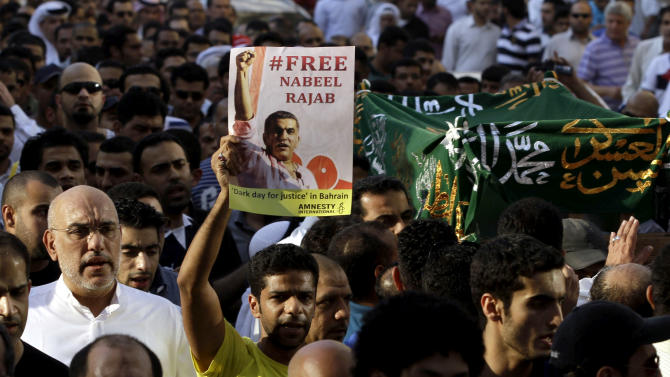 A Bahraini man holds up a sign calling for the release of human rights activist Nabeel Rajab during the funeral procession for Rajab's elderly mother in Manama, Bahrain, on Thursday, Oct. 4, 2012. Rajab, who is serving a three year jail sentence for organizing and participating in unauthorized pro-democracy protests, was allowed out for the day for his mother's funeral. (AP Photo/Hasan Jamali)