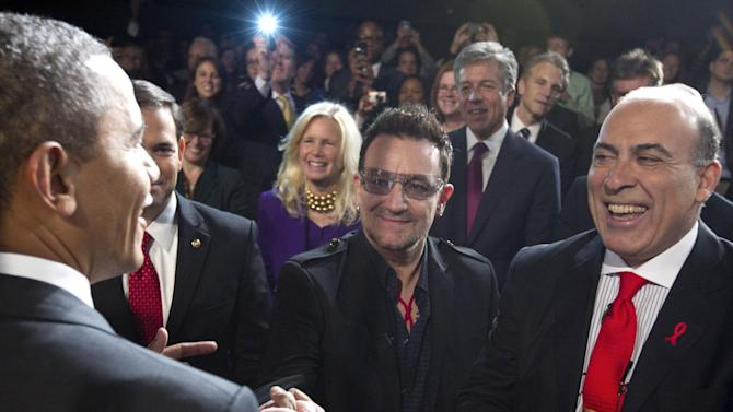 FILE - This is a Thursday, Dec. 1, 2011  file photo of President Barack Obama as he greets U2 front man Bono, center, and Muhtar Kent the chairman of the Board and chief executive officer of The Coca-Cola Company, right, after speaking during a World AIDS Day event at George Washington University in Washington. (AP Photo/Carolyn Kaster, File)