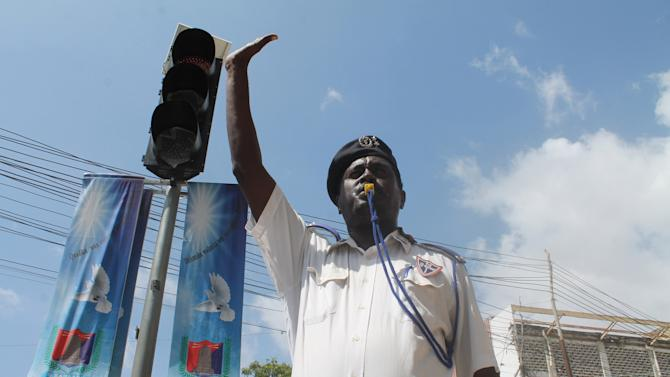 """In this photo taken,Wednesday, Dec, 4, 2013. A Somali traffic police man raises his hand and stands near a street signal to try and stop cars as the traffic light flashes red. Mogadishu in recent months has started to install road signs for the first time after decades of lawlessness left a culture of """"anything goes"""" on the road. Large parts of the country's residents are unfamiliar with traffic laws, increasing the pressure on traffic police struggling to impose law and order in a dangerous and chaotic city. (AP Photo/Farah Abdi Warsameh)"""