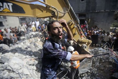 A Palestinian policeman reacts as rescue workers search for victims under the rubble of a house in Rafah