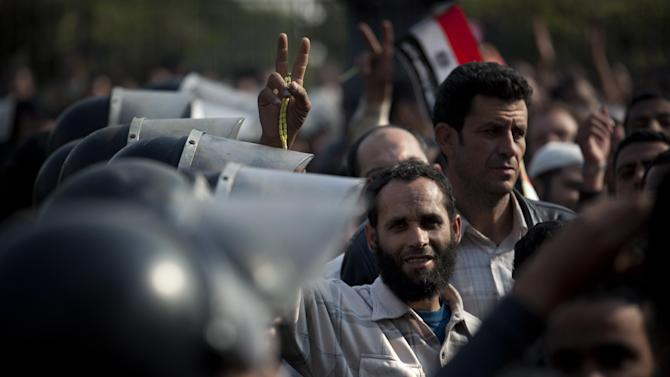 """A Supporter of Egyptian President Mohammed Morsi flashes the Victory sign, as riot police gurad the entrance of Egypt's top court, in Cairo, Egypt, Sunday, Dec. 2, 2012. Egypt's top court announced on Sunday the suspension of its work indefinitely to protest """"psychological and physical pressures,"""" saying its judges could not enter its Nile-side building because of the Islamist president's supporters gathered outside. (AP Photo/Nasser Nasser)"""
