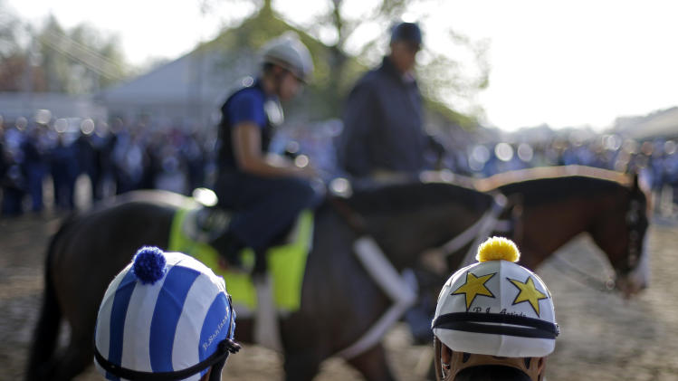 Some jockeys watch as Kentucky Derby hopeful Oxbow walks to the track for a workout at Churchill Downs Wednesday, May 1, 2013, in Louisville, Ky. (AP Photo/David Goldman)
