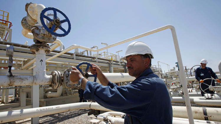 FILE - In this May 31, 2009 file photo, an employee works at the Tawke oil fields in the semiautonomous Kurdish region in northern Iraq. An Iraqi Kurdish official says the country's self-ruled northern Kurdish region has suspended oil exports over a payment row with the central government in Baghdad. (AP Photo/Hadi Mizban, File)