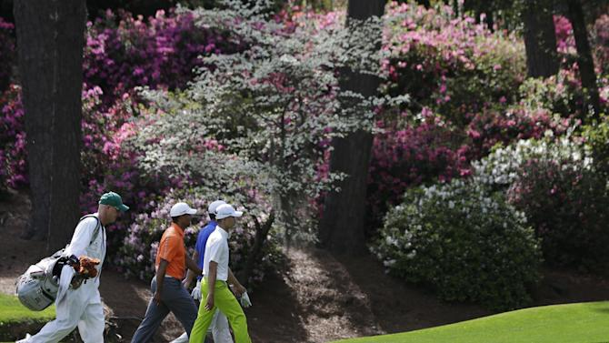 Tiger Woods, left, walks with Amateur Guan Tianlang, of China, and Dustin Johnson on the 13th fairway during a practice round for the Masters golf tournament Monday, April 8, 2013, in Augusta, Ga. (AP Photo/Darron Cummings)