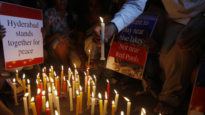 People hold placards during a candlelight vigil at one of the two bomb blast sites, in Hyderabad, India, Friday, Feb. 22, 2013. Indian police are investigating whether a shadowy Islamic militant group was responsible for a dual bomb attack that killed 16 people outside a movie theater and a bus station in the southern city of Hyderabad, a police official said Friday. (AP Photo/Aijaz Rahi)