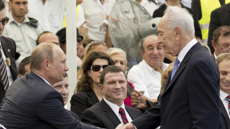 Russian President Vladimir Putin, left, and Israeli President Shimon Peres, right, shake hands during an inauguration ceremony of a memorial to Red Army veterans of World War II in Netanya, Israel, Monday June 25, 2012. The West's standoff with Iran over its nuclear program was expected to top the agenda on Monday as Russian President Vladimir Putin began a 24-hour visit to Israel. (AP Photo/Jack Guez, Pool)