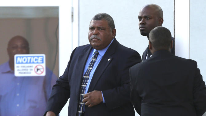 Kansas City Chiefs head coach Romeo Crennel, left, leaves a memorial service for Kansas City Chiefs' Jovan Belcher at the Landmark International Deliverance and Worship Center Wednesday, Dec. 5, 2012 in Kansas City, Mo. Belcher shot his girlfriend, Kasandra Perkins, at their home Saturday morning before driving to Arrowhead Stadium and turning the gun on himself.  (AP Photo/Ed Zurga)