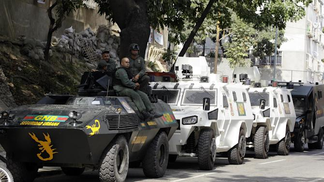 Venezuelan National Guard soldiers and vehicles sit along a street near downtown Caracas, Venezuela, Monday, April 15, 2013. Venezuela's government-friendly electoral council indicated Monday it would quickly certify the presidential victory of Hugo Chavez' hand-picked successor Nicolas Maduro, apparently ignoring opposition demands for a recount in Sunday's tight race. (AP Photo/Fernando Llano)