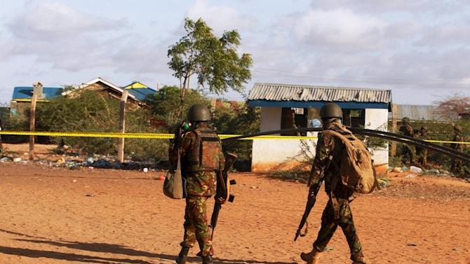 Kenya Defence Forces soldiers walk near the scene of an overnight attack on a residential complex in Mandera town at the Kenya-Somalia border