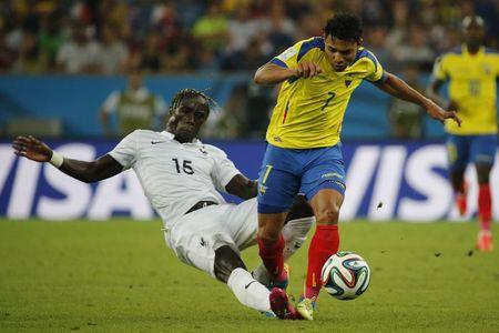 France's Sagna fights for the ball with Ecuador's Montero during their 2014 World Cup Group E soccer match at the Maracana stadium in Rio de Janeiro