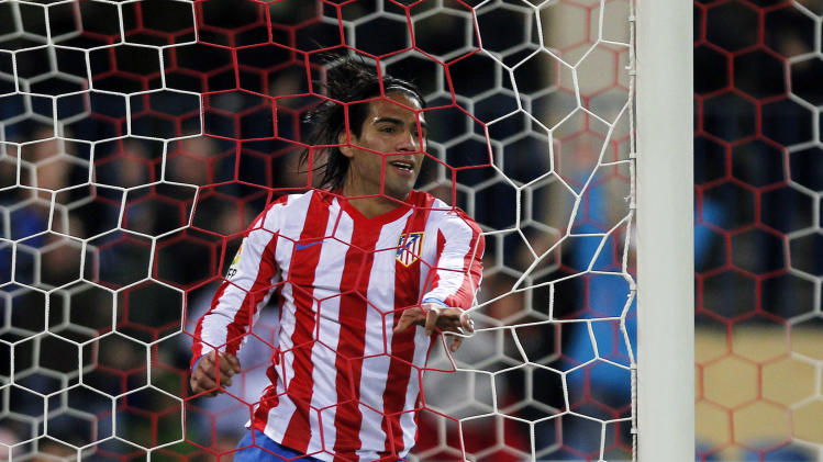 Atletico de Madrid's Radamel Falcao from Colombia, holds the net after missing a chance during a Spanish La Liga soccer match against Osasuna at the Vicente Calderon stadium in Madrid, Spain, Sunday, Oct. 28, 2012. (AP Photo/Andres Kudacki)