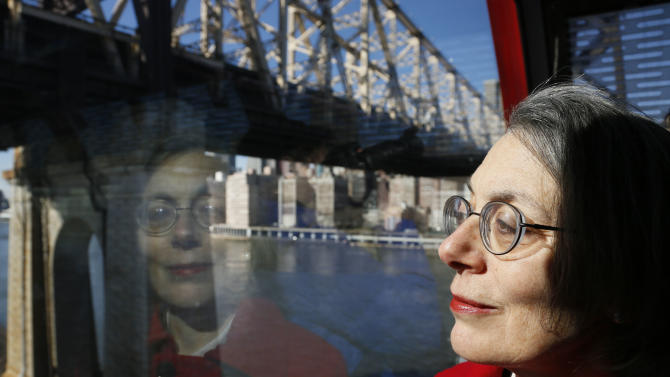 Janet Falk, public relations professional, rides the Roosevelt Island tramway with a Manhattan view behind her on Thursday, Feb. 21, 2013 in New York.  Falk applied for a public-relations job at a New York City law firm two years ago, but the recruiter told her she wouldn't be considered because she had been unemployed for more than three months, Falk said. (AP Photo/Bebeto Matthews)