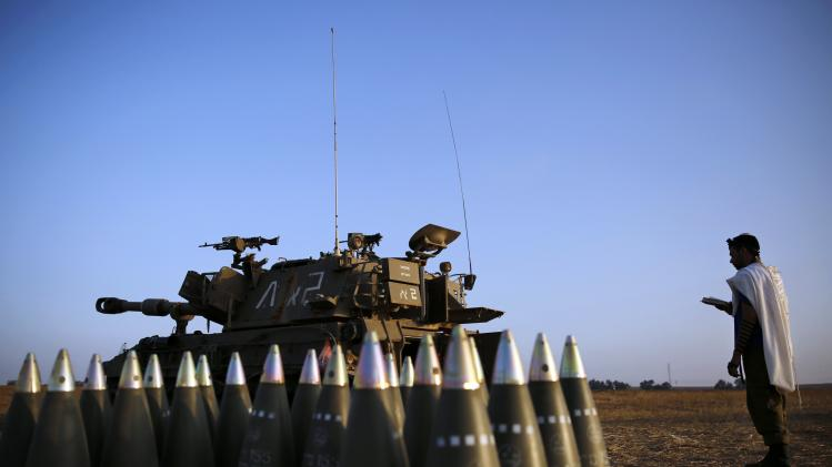 An Israeli soldier prays beside a mobile artillery unit and shells in a field near the central Gaza Strip