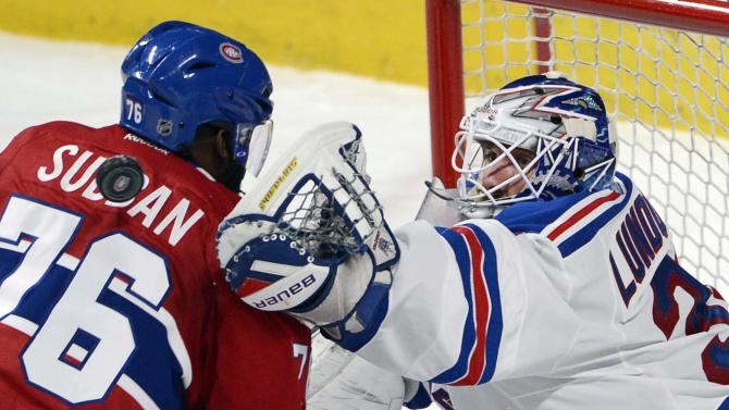 New York Rangers goalie Henrik Lundqvist, right, reaches for a loose puck around Montreal Canadiens defenceman P.K. Subban (76) during the second period in Game 1 of the Eastern Conference finals in the NHL hockey Stanley Cup playoffs against in Montreal on Saturday, May 17, 2014. (AP Photo/The Canadian Press, Adrian Wyld)