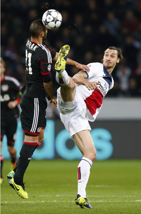 Bayer Leverkusen's Toprak challenges Paris St Germain's Ibrahimovic during their Champions League soccer match in Leverkusen
