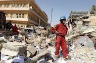 Iraqi security forces and rescue workers inspect the damage following a bomb attack at the Shiite endowment headquarters in Baghdad. The attacks came amid a dispute between the two Muslim endowments which manage Iraq&#39;s religious landmarks over a shrine north of Baghdad