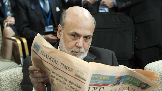 Ben Bernanke, chairman of the Federal Reserve, reads a newspaper before a meeting of the IMFC, during the World Bank/IMF Annual Meetings at IMF headquarters, Saturday, Oct. 12, 2013, in Washington. World finance officials prepared to wrap up three days of meetings in Washington, where fretting about the risk of an unprecedented U.S. debt default overshadowed myriad worries about a shaky global economic recovery. ( AP Photo/Jose Luis Magana)