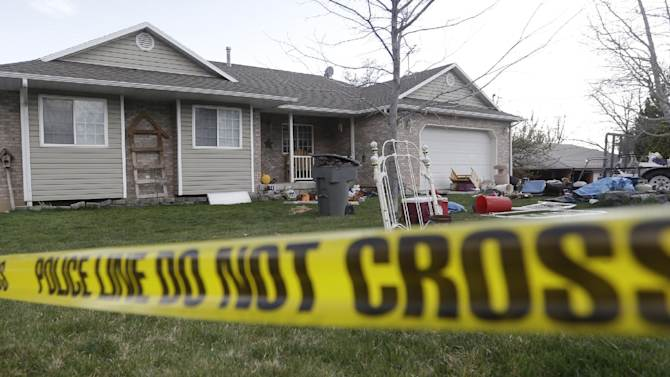 In this April 13, 2014, photo, Pleasant Grove Police police tape is shown in front of the scene where seven infant bodies were discovered and packaged in separate containers at a home in Pleasant Grove, Utah. Authorities say a Utah woman accused of killing six babies that she gave birth to over 10 years told investigators that she either strangled or suffocated the children and then put them inside boxes in her garage. According to a probable cause statement released by police Monday, Megan Huntsman said that between 1996 and 2006, she gave birth to at least seven babies at her home and that all but one of them were born alive. (AP Photo/Rick Bowmer)
