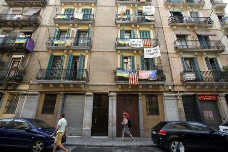 Banners against touristic apartments hang from balconies as people walk past them at Barceloneta neighborhood in Barcelona